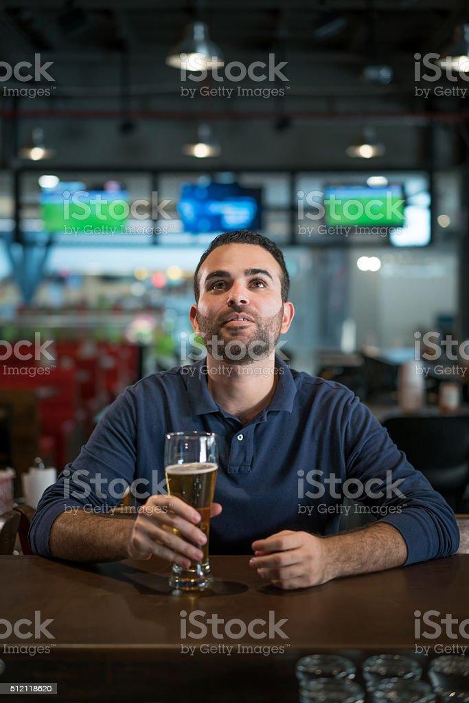 Man watching football at the bar stock photo
