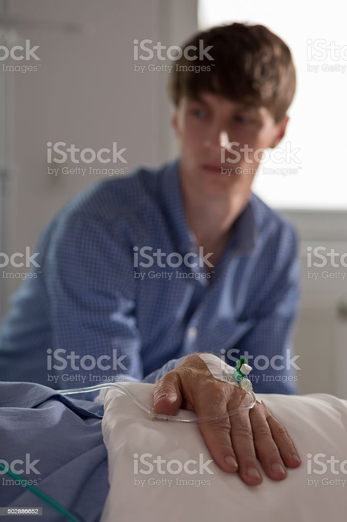 Man watching his ill father stock photo
