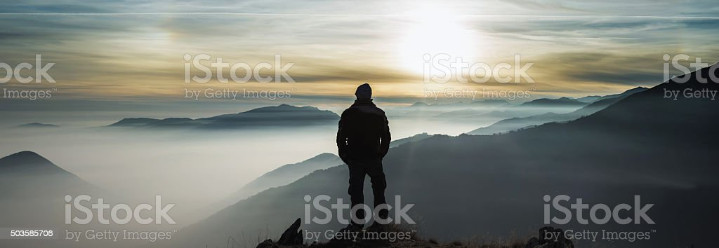 Man watching mountains clouds from a peak stock photo