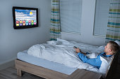 Man Watching Television In His Bedroom