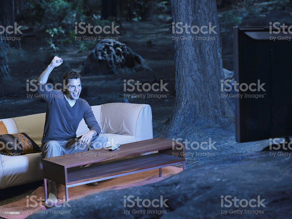 A man watching television outdoors in the woods royalty-free stock photo