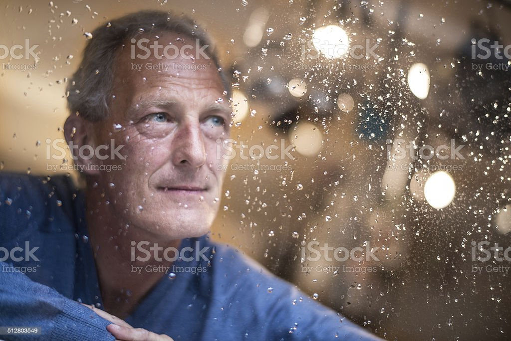 Man at home watching the pouring rain