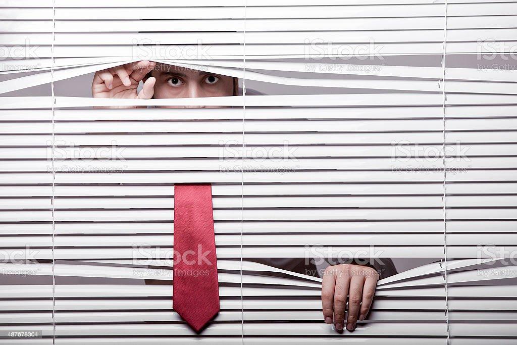 Man Watching through window blinds stock photo