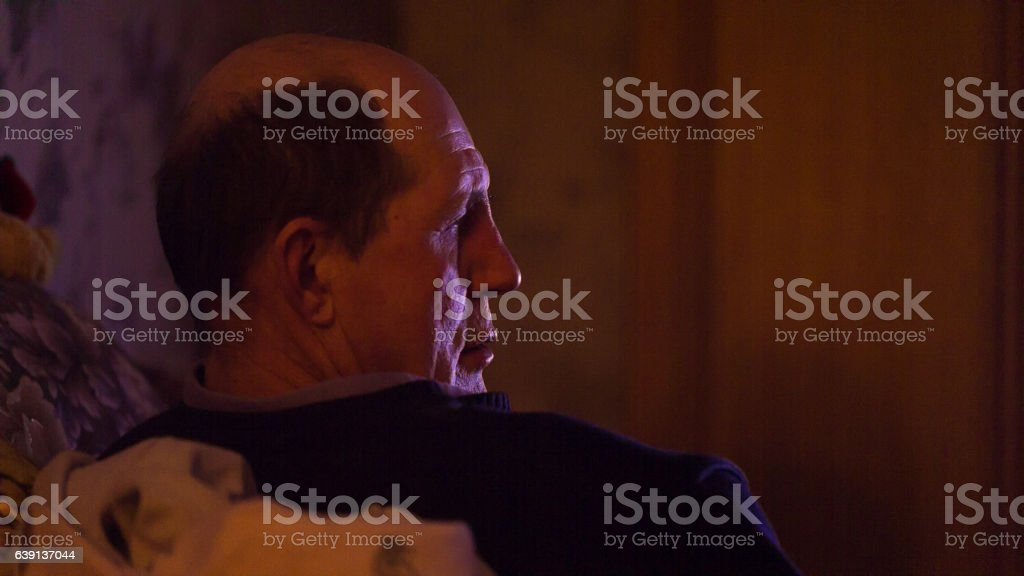 Man watching TV and talking close-up stock photo