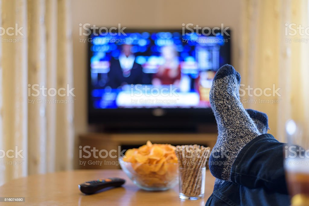 man watching TV (television) news with feet on table stock photo