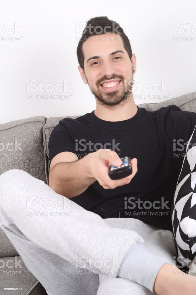 Man watching tv on couch. stock photo