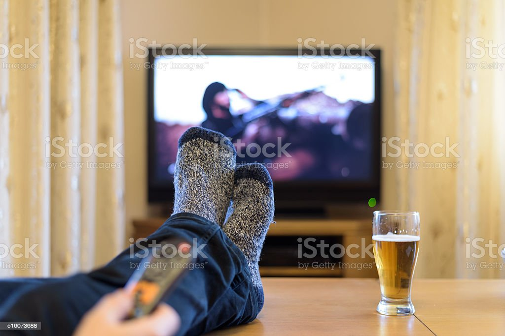 man watching TV (man with gun) with feet on table stock photo