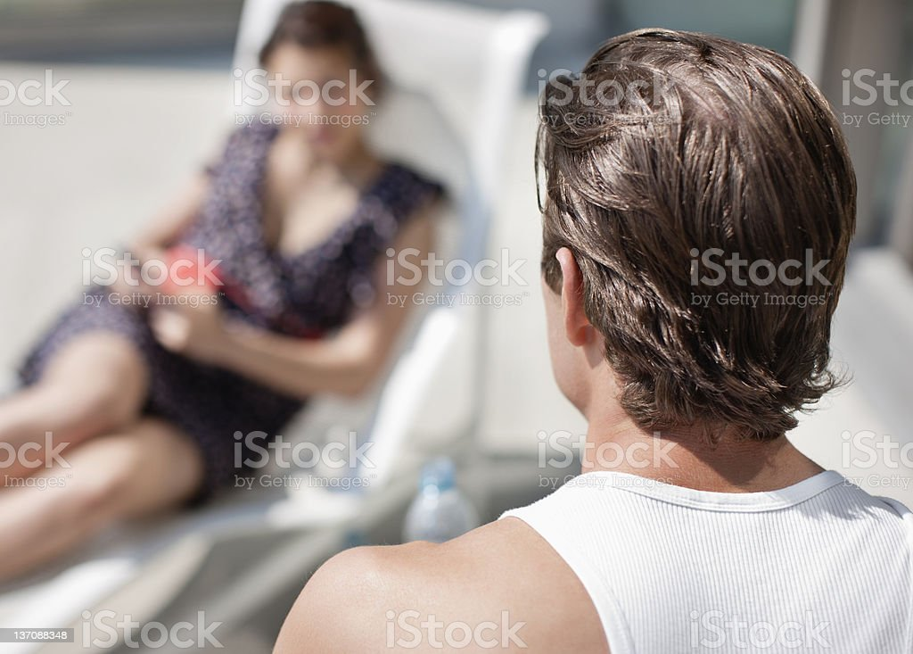 Man watching woman on lounge chair stock photo