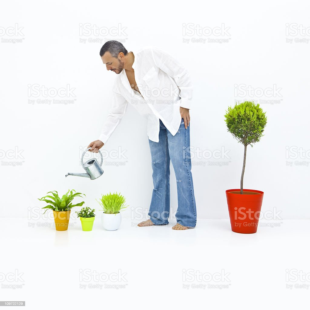 Man watering his plants in a white home royalty-free stock photo