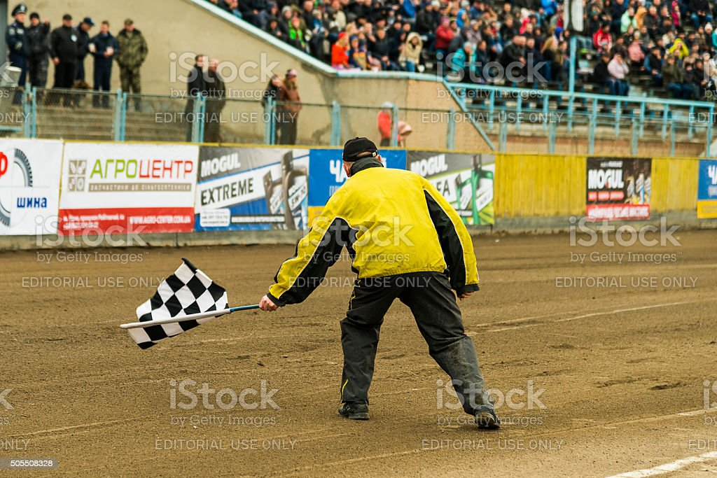Man waves the checkered flag at the finish line stock photo