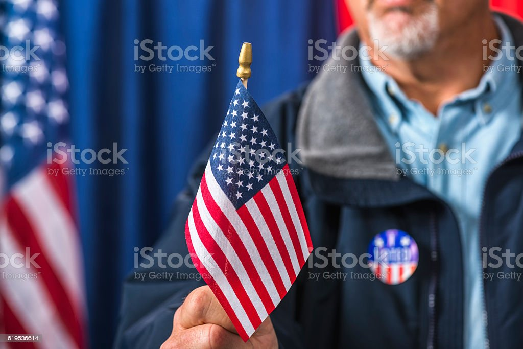 Man waving a small American flag after he voted stock photo