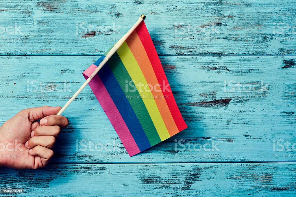 man waving a small rainbow flag stock photo