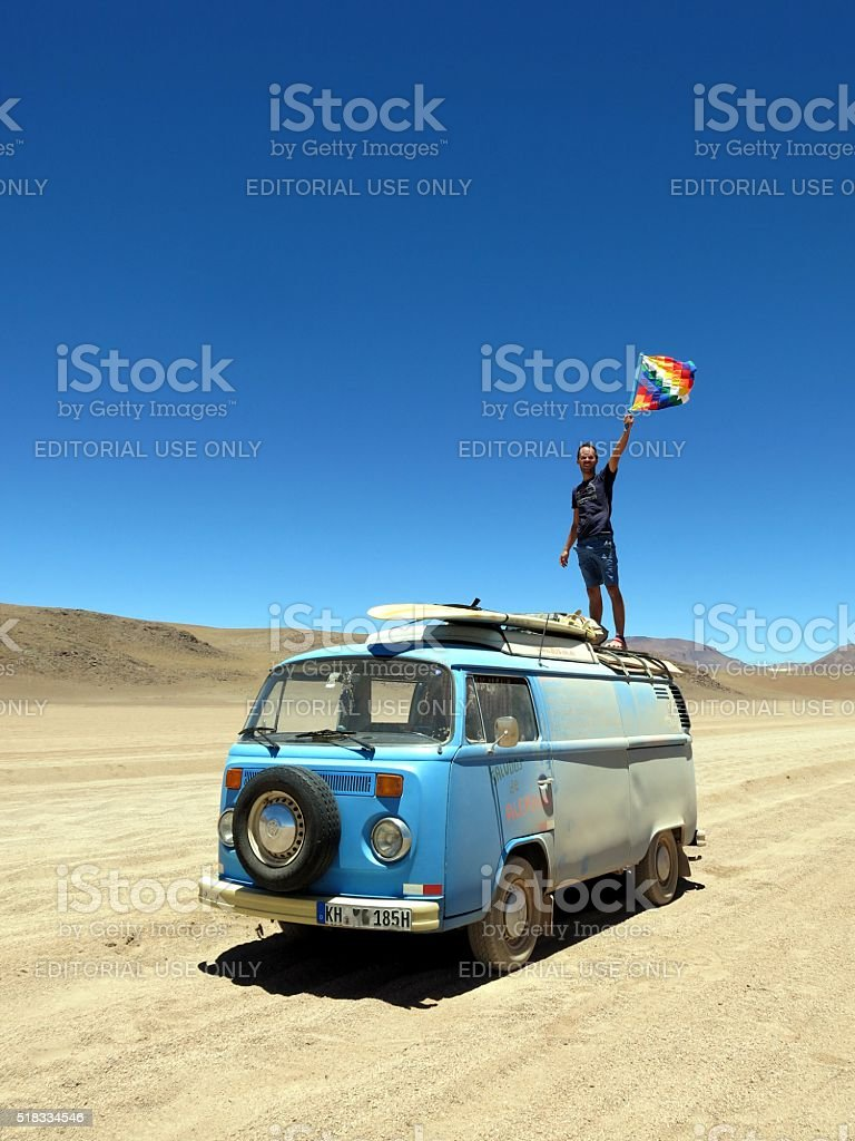Man waving aymara flag on top of VW bus stock photo