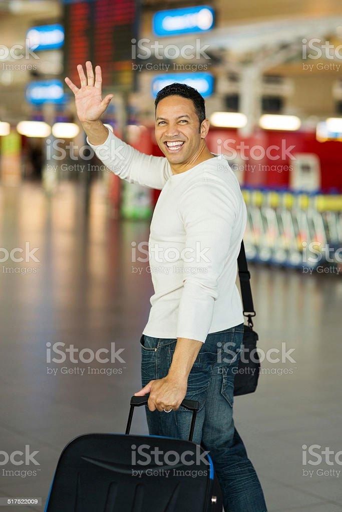 man waving goodbye at airport stock photo