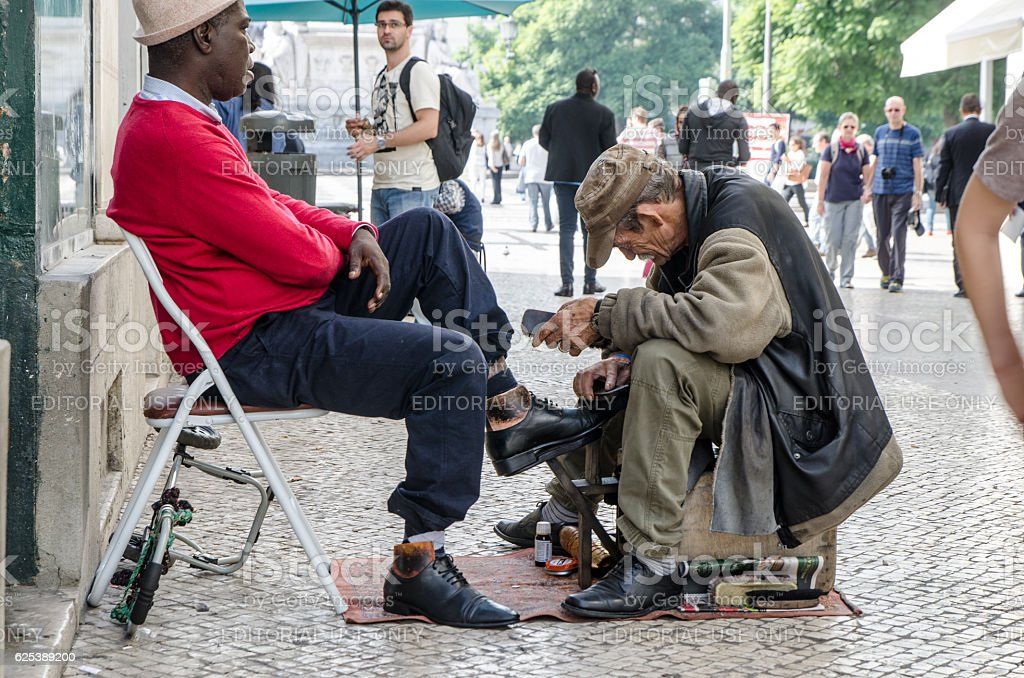 Man waxing and cleaning shoes of customer in street Lisbon stock photo