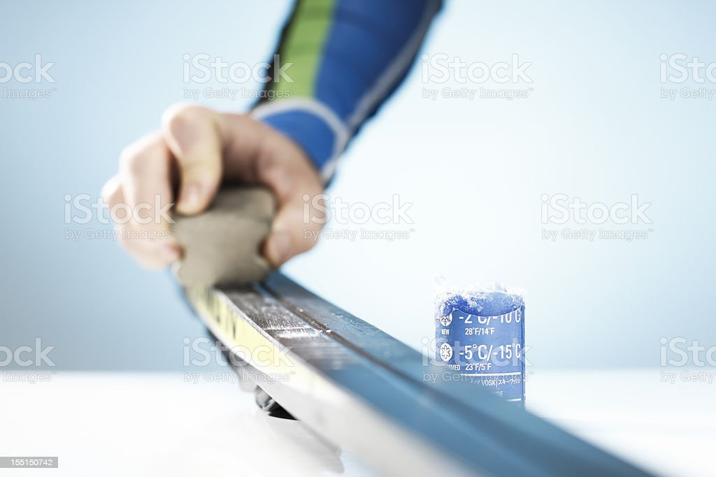 Man waxing his cross-country skis on a table royalty-free stock photo