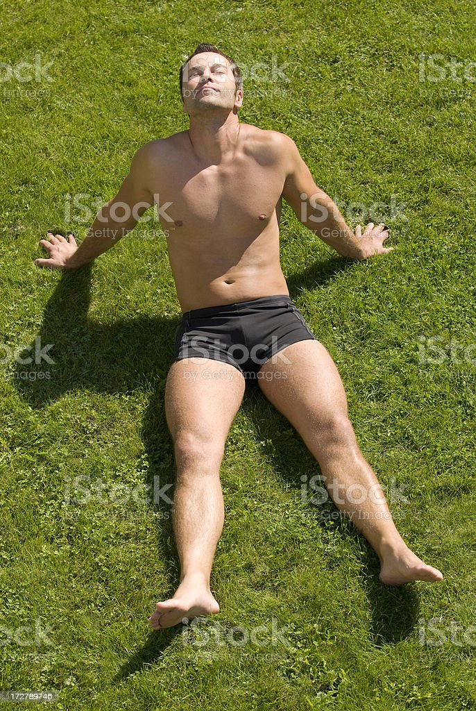 Man wearing a bathing suit, sunbathing on the grass. royalty-free stock photo