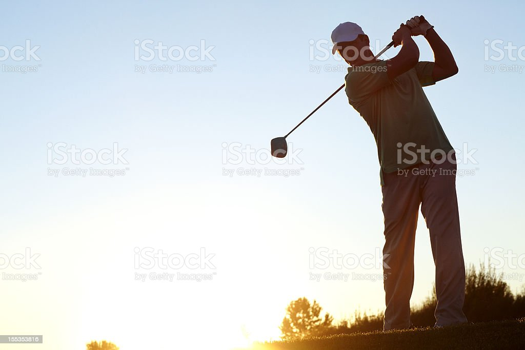Man wearing a hat playing golf at sunset royalty-free stock photo