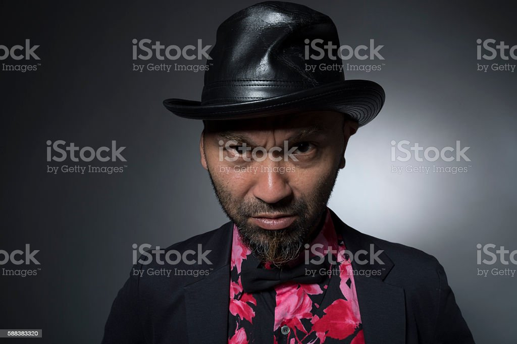 Man wearing a hat that is staring from disgust stock photo