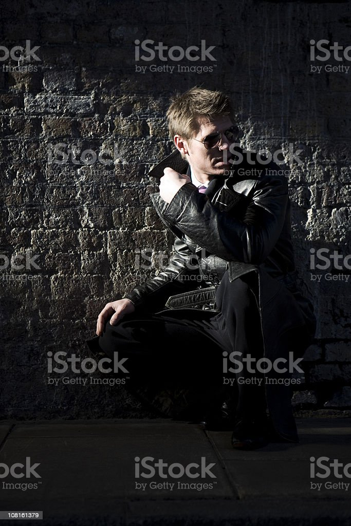 Man wearing a leather jacket sitting in front of brick wall royalty-free stock photo