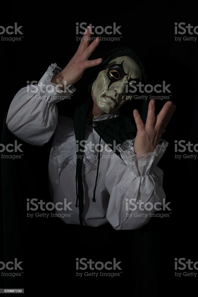 Man wearing a mask and a green cloak. stock photo