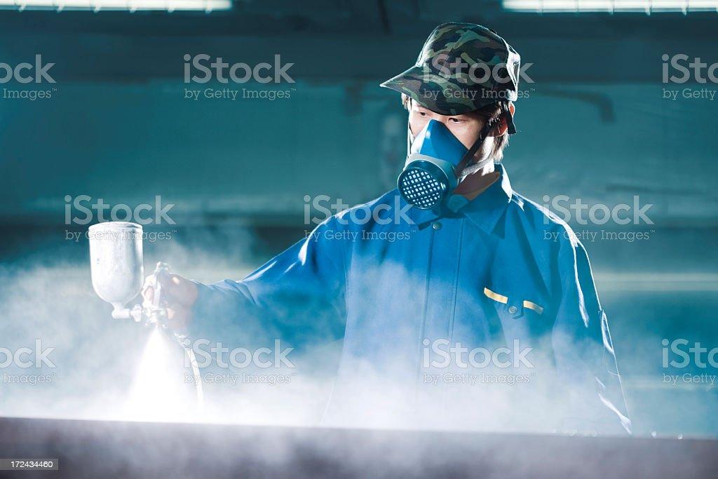 A man wearing a mask holding a spray gun stock photo