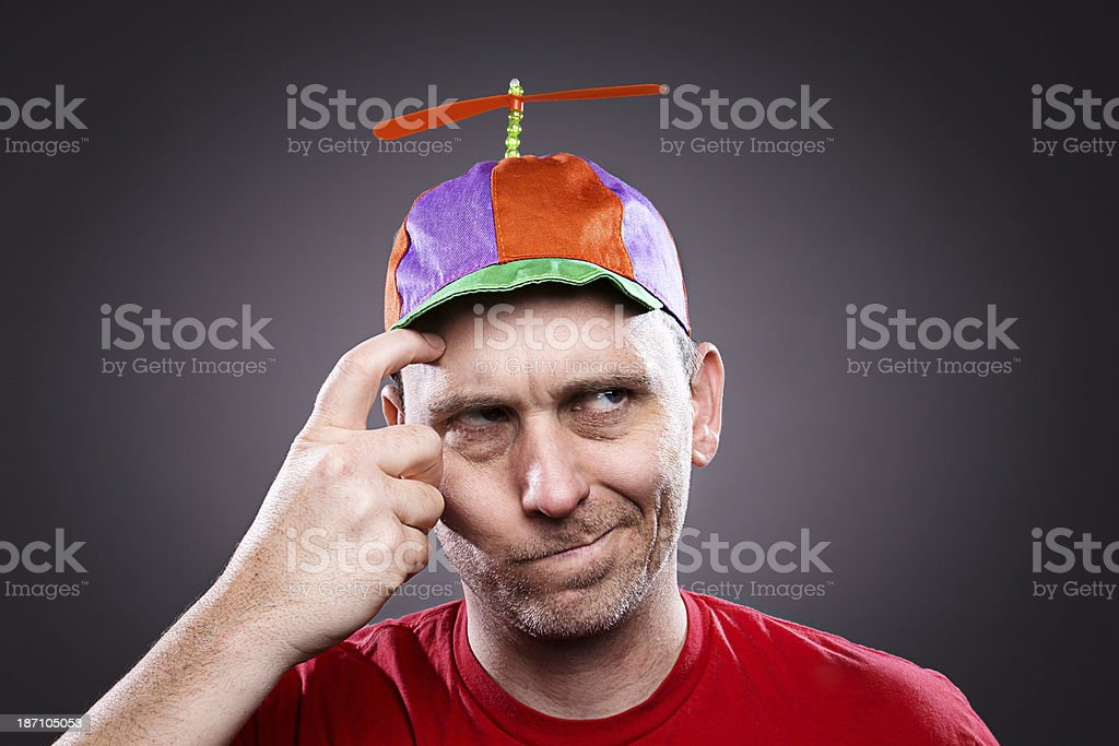 Man wearing a propeller beanie thinking and scratching his head stock photo