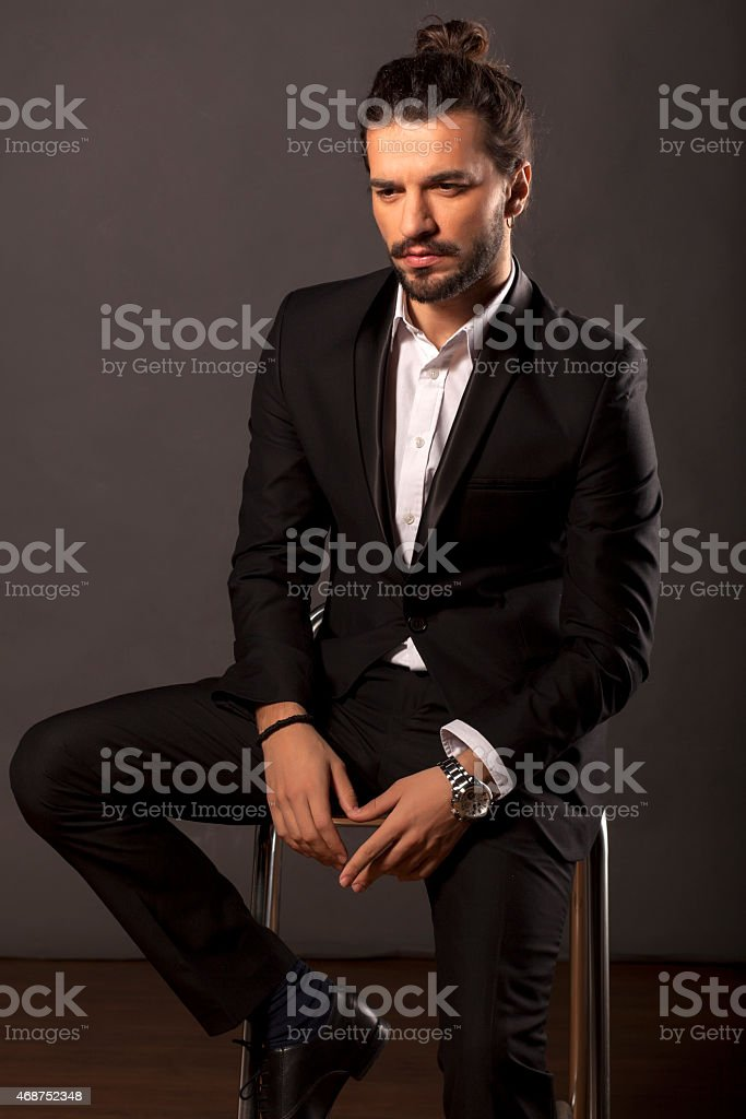 A man wearing a suit sitting on a stool stock photo