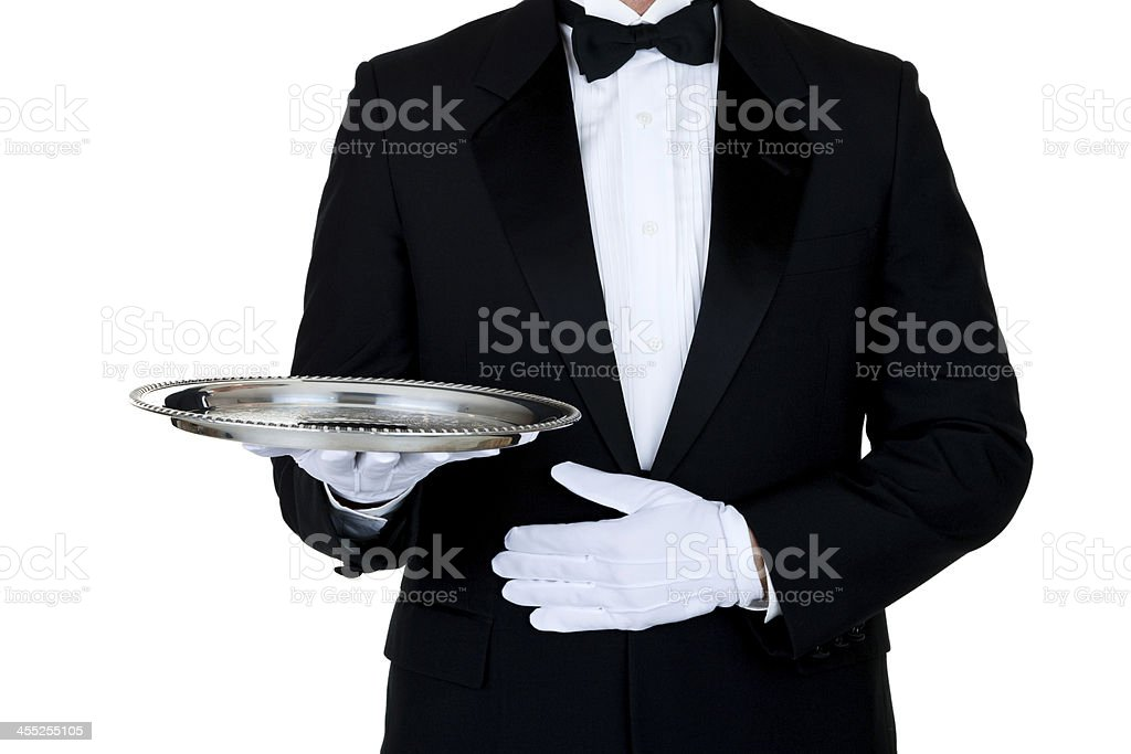 Man wearing a tuxedo and holding serving tray stock photo