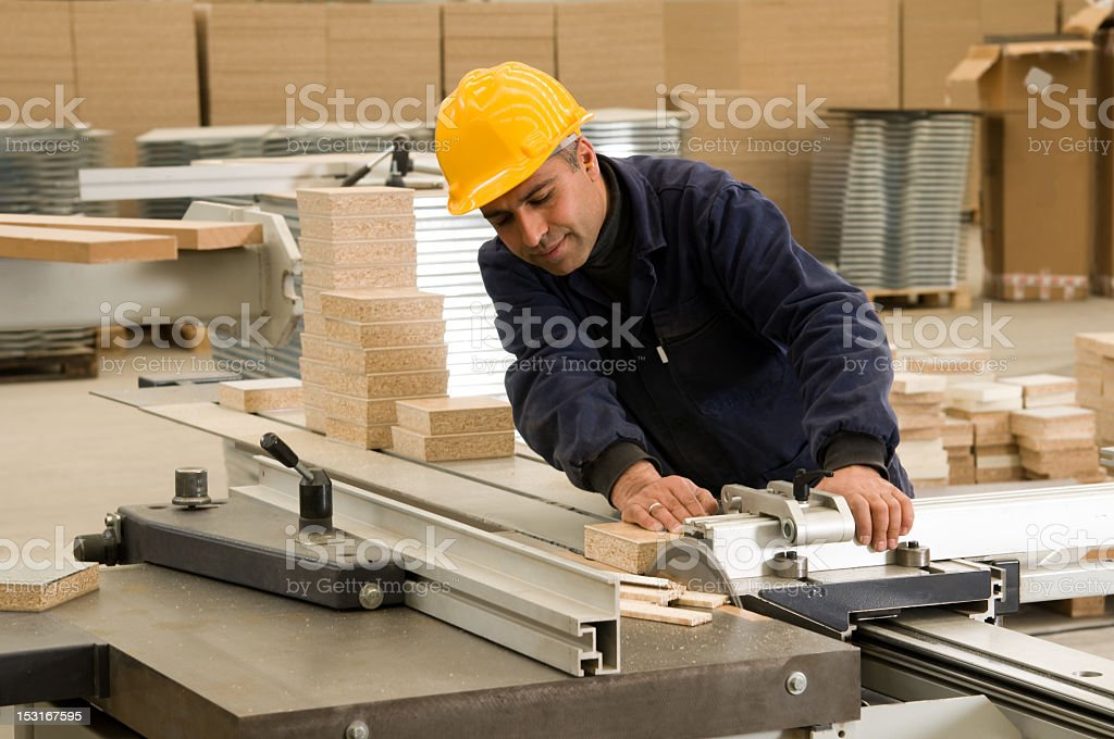A man wearing a yellow safety hat cutting a piece of wood stock photo