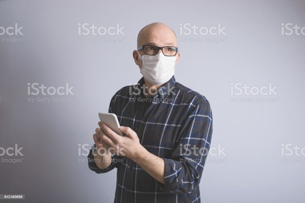 Man Wearing Air Pollution Face Mask Using Smart Phone stock photo