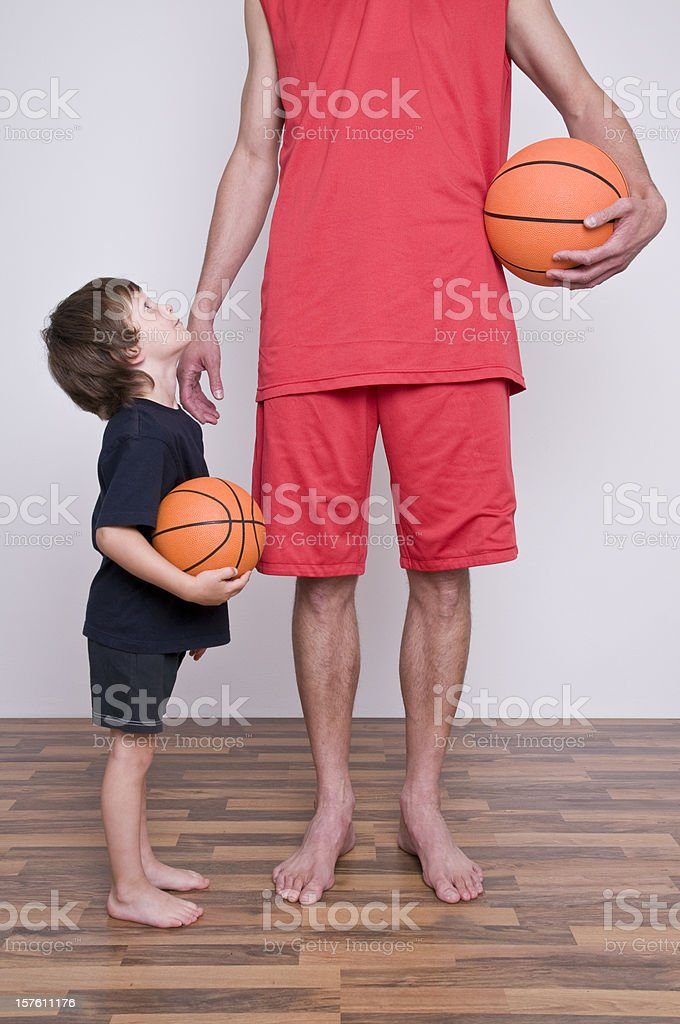 A man wearing all red holding a basketball next to a child stock photo