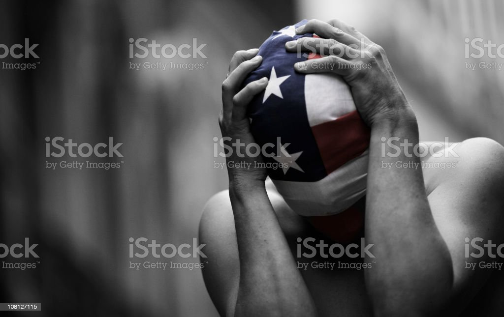 Man WEaring American Flag As Mask And Holding Head royalty-free stock photo