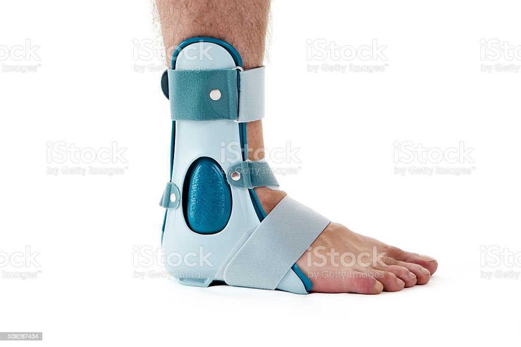 Man Wearing Ankle Support Cast in White Studio. stock photo