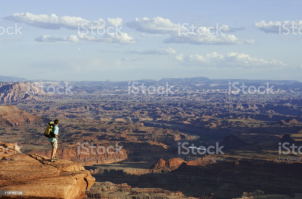 Man Wearing Backpack Standing On Rocky Ledge Looking At View royalty-free stock photo