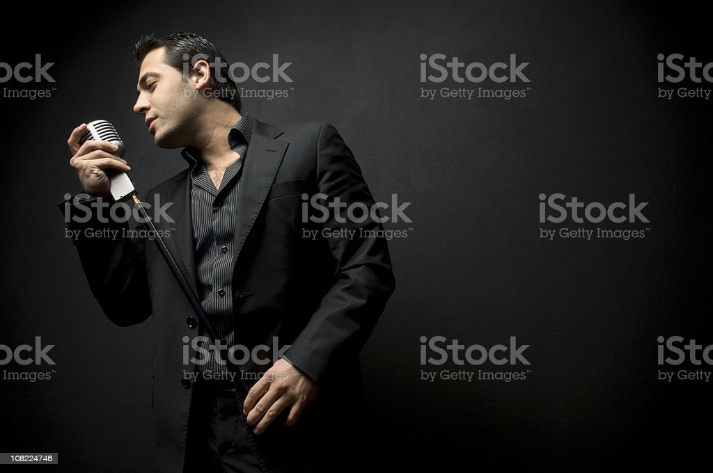 Man Wearing Black Suit Singing into Old Style Microphone royalty-free stock photo