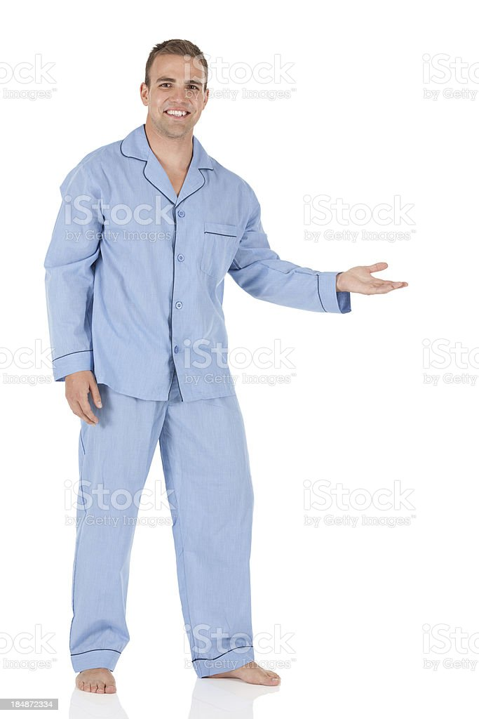 Man wearing blue pajamas and presenting stock photo