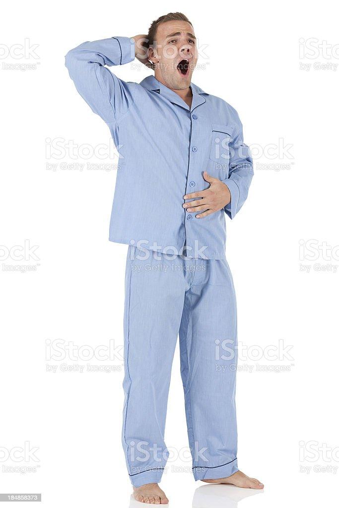 Man wearing blue pajamas and yawning stock photo