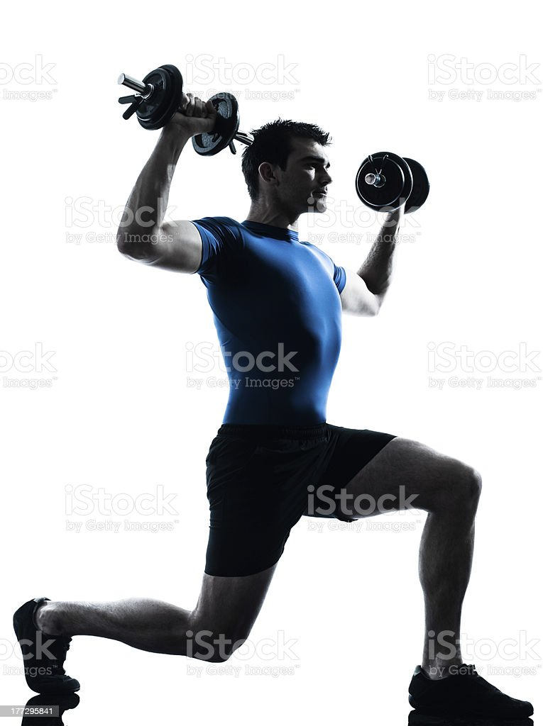 A man wearing blue shirt lifting weights while working out  royalty-free stock photo