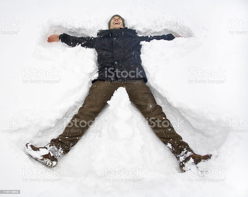 Man wearing brown and blue making a snow angel stock photo