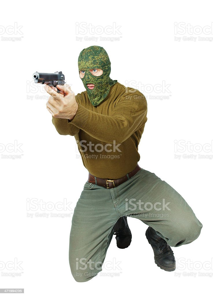 Man wearing camouflage mask is aiming with a pistol royalty-free stock photo