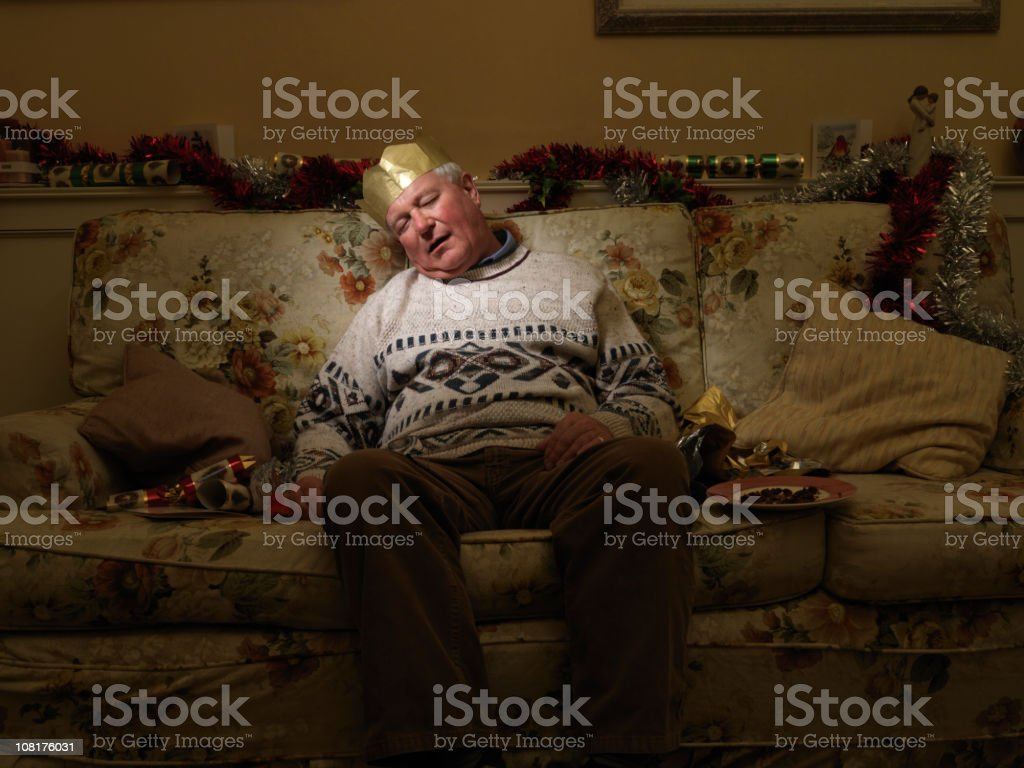 Man Wearing Christmas Hat, Sleeping on couch stock photo