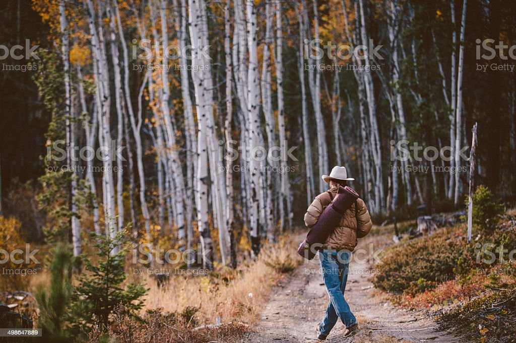 Man wearing cowboy hat carries mat while walking in woods stock photo