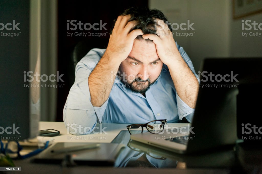 Man wearing exasperated expression while looking at laptop royalty-free stock photo