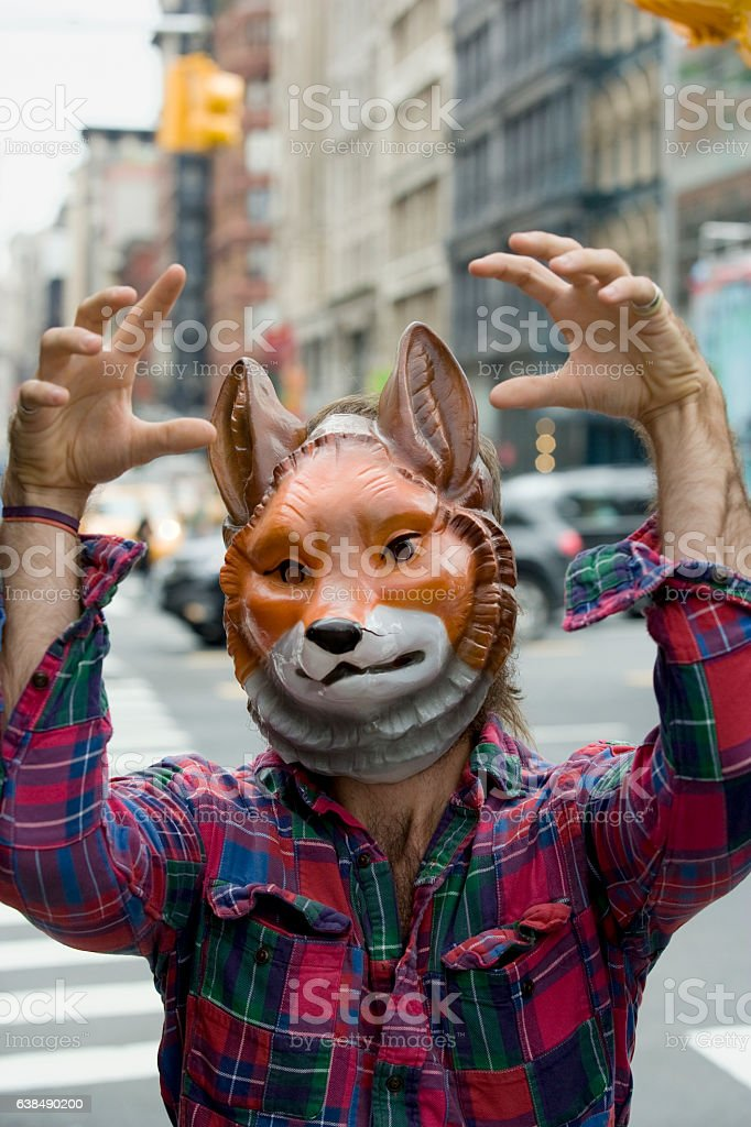 Man wearing fox mask acting silly in downtown city stock photo