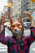 Man wearing fox mask acting silly in downtown city