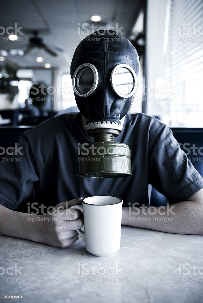 Man Wearing Gas Mask and Drinking Coffee in Diner royalty-free stock photo