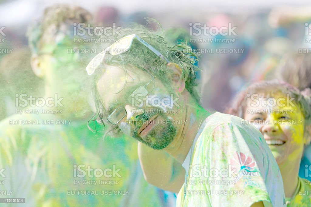 Man wearing glasses and beard covered with green color powder stock photo