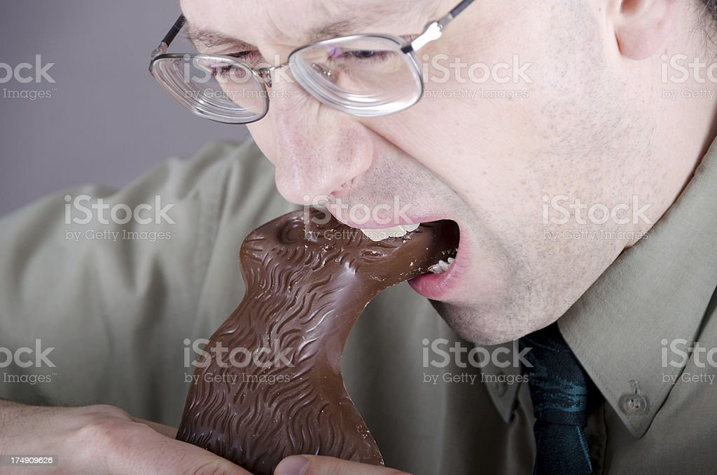 Man wearing glasses biting down hard on Easter bunny ears. royalty-free stock photo
