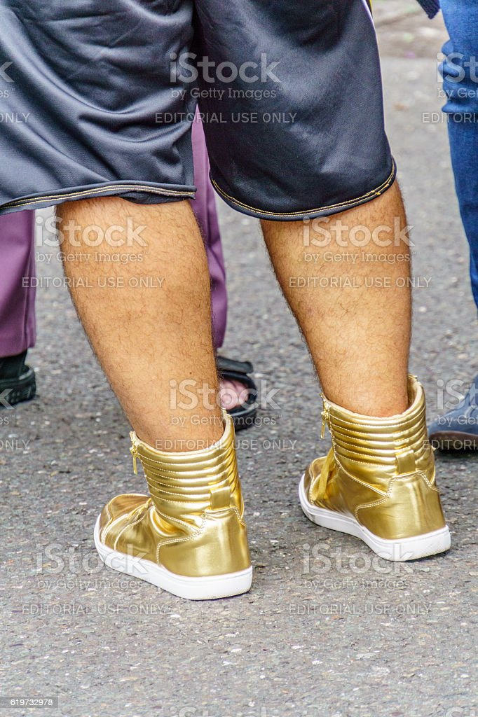 Man wearing gold boots stock photo